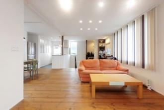 キッチンとリビングを離すことで、家事の音が気にならない間取り。床板はツーバイ材を使用。壁は光を広げる白色で統一しました。近所の視線を気にせずに 心ゆくまで窓外の眺めを楽しむため、2階リビングの家に中古リノベーション。設計も性能も新築を超える出来映え。キッチンとリビングを離して、家事の音が気にならない間取り。床板はツーバイ材。玄関ホールの吹き抜けに面したキッチン、収納は隠しできる引き戸仕様。土足でも使えるシューズクローク、自転車も置ける土間玄関。施工はアルティザン建築工房