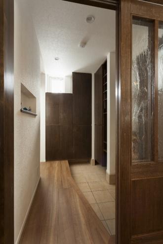 玄関にはコートやゴルフバッグなどを入れる大型収納。ドアには特注建具の府連巣性の輸入ガラス。玄関フードを付けず、冷気を引き戸でシャットアウトするスタイル。フルリフォーム。株式会社リビングワーク