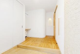 アールにデザインされた壁がある玄関。札幌の高断熱・高気密化のリノベーションにより長期優良住宅先導モデルとして認められた、住宅の外気温に左右されない安定した室内環境を体感できるモデルハウス。パイン材の床に塗り壁とエコカラットの質感のあるアクセントウオール。アールデザインの玄関土間。市松に敷かれた琉球畳がおしゃれな和室。下は大容量の収納。レンジ横や出入り口の柱などにはアクセントにタイルを部分張り。施工はリビングワーク。