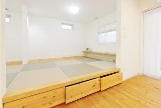 琉球畳がおしゃれな和室。札幌の高断熱・高気密化のリノベーションにより長期優良住宅先導モデルとして認められた、住宅の外気温に左右されない安定した室内環境を体感できるモデルハウス。パイン材の床に塗り壁とエコカラットの質感のあるアクセントウオール。アールデザインの玄関土間。市松に敷かれた琉球畳がおしゃれな和室。下は大容量の収納。レンジ横や出入り口の柱などにはアクセントにタイルを部分張り。施工はリビングワーク。