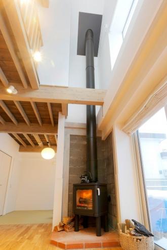 薪ストーブ。ブロック構造をそのまま現して、薪ストーブのコーナーに。吹き抜けに伸びる煙突がダイナミックな印象。株式会社アルティザン建築工房