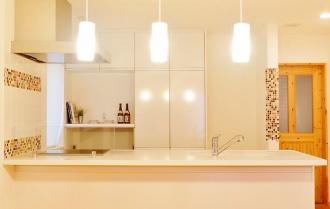 開放的なキッチン。札幌の高断熱・高気密化のリノベーションにより長期優良住宅先導モデルとして認められた、住宅の外気温に左右されない安定した室内環境を体感できるモデルハウス。パイン材の床に塗り壁とエコカラットの質感のあるアクセントウオール。アールデザインの玄関土間。市松に敷かれた琉球畳がおしゃれな和室。下は大容量の収納。レンジ横や出入り口の柱などにはアクセントにタイルを部分張り。施工はリビングワーク。