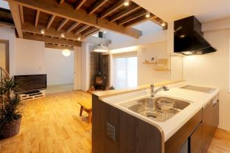 オープンキッチン。腰壁と収納を造作。ブロック構造を残して白く塗装し、間接照明をプラス。1階天を兼ねた2階床にはツーバイ材を使用。株式会社アルティザン建築工房