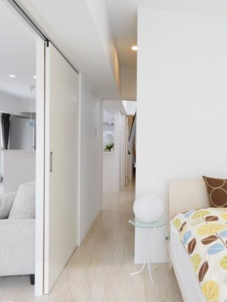 回遊動線で結んだ玄関・リビング・寝室。札幌の中古リノベーションマンションの事例を紹介。マンションを購入し、SAWAI建築工房にリノベーションを依頼。収納や動線にも細やかな配慮が行き届いたプラン。L字型キッチン、2方向から光が入るLDK、工夫で専有面積以上の広さ。内窓は遮音性にも優れた断熱サッシ。交通量が多くても、静かな住まい。