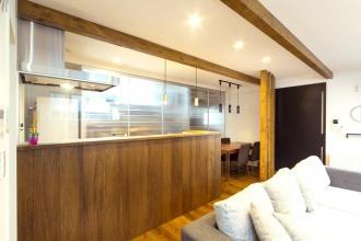 キッチンは無垢材の素材感がいい。高さのある天井、奥行きを強調する構造梁、落ち着いた色合いの床や柱、自然光や照明を室内に広げる白い壁、空間の表情を引き締める黒いアイアン階段。S様ご夫婦がリノベーションプランで一番こだわった「クールでスタイリッシュ」な空間がアルティザンの提案で完成しました。【札幌市西区の戸建て中古住宅リノベーション】施工はアルティザン建築工房