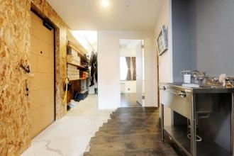 玄関・土間収納。サーファーハウス、コンクリート打ちっぱなしの壁やユーズドの足場板などインダストリアルにとことんこだわった札幌市の中古マンション+リノベーション実例。DIYのアイディアも豊富。参考になる土間収納やリビングのハンモック。高さの違うオリジナル造作棚は矢印のかたちに。キッチンは特注。ステンレス天板。アイアン塗装。唯一無二の個性的な空間。施工は株式会社北王リフォーム事業部RELIFE