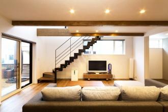 広い空間に、アクセントの梁やアイアンが引き締めるリビング。高さのある天井、奥行きを強調する構造梁、落ち着いた色合いの床や柱、自然光や照明を室内に広げる白い壁、空間の表情を引き締める黒いアイアン階段。S様ご夫婦がリノベーションプランで一番こだわった「クールでスタイリッシュ」な空間がアルティザンの提案で完成しました。【札幌市西区の戸建て中古住宅リノベーション】施工はアルティザン建築工房