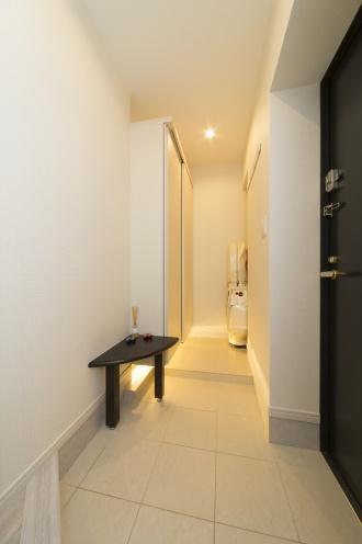 足元に照明のある玄関。子どもが独立し、リフォーム。換気と断熱を第一に考えた、スケルトンリフォームです。二重床下地の採用によるキッチンや暖房の位置変更。天井を下げて各部屋にダウンライトを設置。風の通り道を確保し、各所にエコカラットを採用。浴室の壁もホーローを採用。水を流すだけでお手入れが楽。