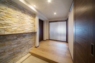広い玄関。住友不動産マンションリフォーム札幌の事例。スケルトンリフォームで根本から課題を解決。寝室と水回りがダイレクトにつながる間取り。ホテルのような生活空間。壁に貼ったイタリア産天然石。