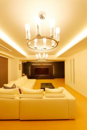 スタイリッシュなインテリア。リビングからキッチンが見えないように壁を造作し採光を兼ねたスリットガラス。TVボードに間接照明を入れて石タイル壁を浮だたせラグジュアリーな雰囲気。天井に間接照明、シャンデリアが上質な空間へ。施工は札幌市のAIS(アイズ)インテリアデザイン。