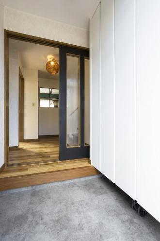 RELIFEのリフォーム事例。北王リフォームの事例。痛んだ外壁と寒い浴室。ヘリンボーンのウッドタイルの床。おしゃれな照明。玄関ホールとダイニングの壁に内窓。土足使用も可能な耐久性のある建材。テーマカラーで統一感のある住まい。浴室の断熱補強。