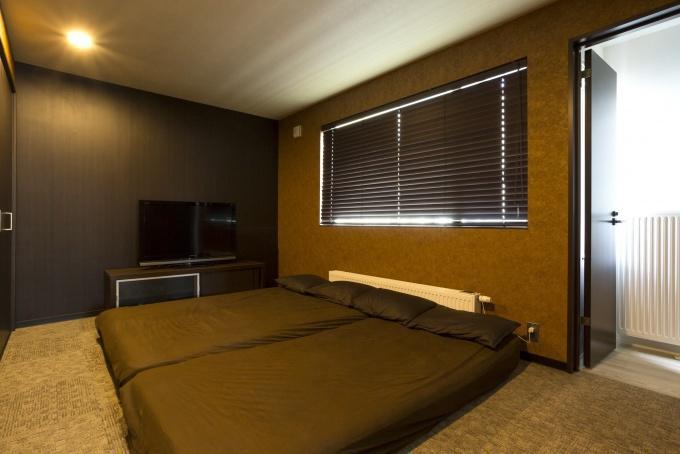 寝室。悠々自適に暮らせる完全分離型の2世帯リフォーム。ブルックリンスタイル。2世帯住宅計画。隠し部屋のような和室。真っ白なキッチン。すりガラスの窓。広々としたユーティリティ。玄関にレザー調のクロス。黒のクロスにエンボス柄のウォークインクローゼット。キーカラーは色数を抑えて渋いトーン。
