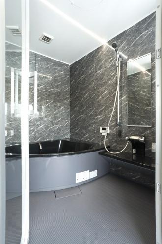 真似したい高級感あふれるバスルーム。水回りは玄関側にあった元の洋室に移し、洗面と浴室の間はガラスにして窓外が眺められるようにしています。位置を大きく変えた分、排水がスムーズに流れるように床を上げ、経路・勾配を計算して施工しています。