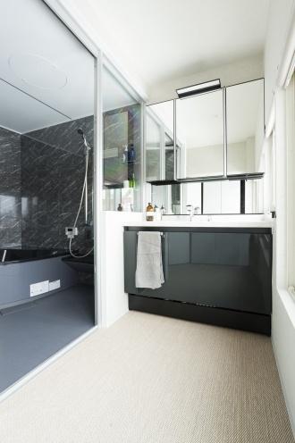 水回りは玄関側にあった元の洋室に移し、洗面と浴室の間はガラスにして窓外が眺められるようにしています。位置を大きく変えた分、排水がスムーズに流れるように床を上げ、経路・勾配を計算して施工しています。