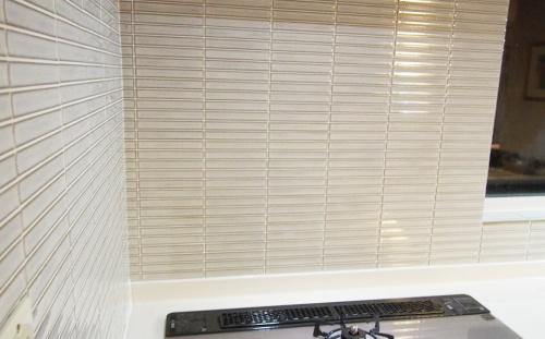 キッチンワークスのリフォーム事例。札幌市清田区のリフォーム。窯変釉を生かしたタイルは汚れにも強く、お手入れ簡単。目地材はキッチン専用の油汚れ防止目地材「スーパークリーンキッチン」を使用。システムキッチンは、LIXILの『サンヴァリエ アレスタ』シリーズへの交換。レンジフードはトクラスの『サイクロンフード』。水平渦巻きによる高い集煙性と、「フロントキャッチ方式」により、内部への油汚れをしっかり抑えます。レンジフード本体は、油をはじく撥油塗装。なめらかな形状と合わせて、拭き掃除が簡単です。標準品ではなく、お客