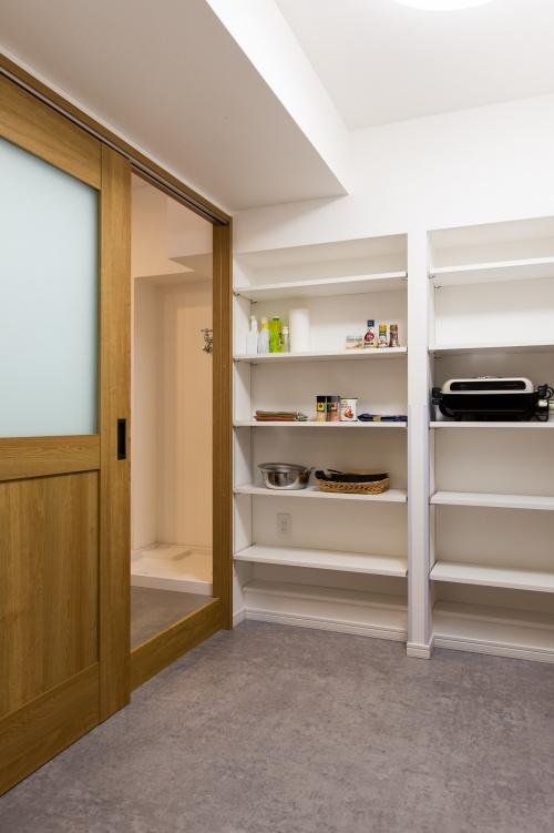 大型パントリーはキッチンと廊下の2 ウェイ。可動式の棚を2面に取り付け、食品に限らないさまざまな生活用品の収納に重宝しています。