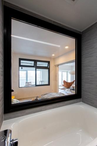 寝室とバスルームの間には、入浴しながら外の景色を楽しめる大きなフィクス窓。