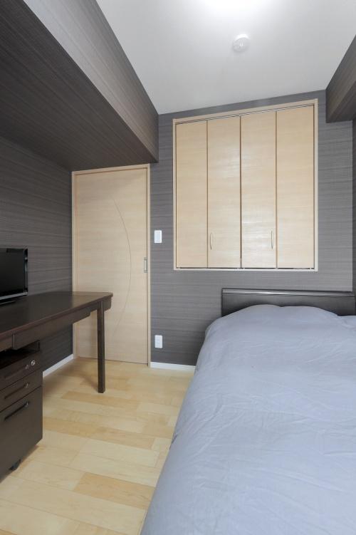 吊り収納は空間を効率的に利用するための工夫。隣の部屋ではこの収納下にスペースが空いており、ベッドの足側を入れています
