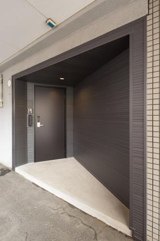 1階倉庫の一部シャッターを玄関ドアに改修。1階にテナントが入居してもいいように、倉庫空間と階段室を仕切って