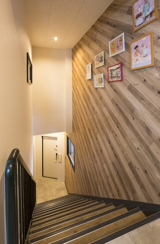 1階出入口と2階玄関をつなぐ階段室の手すりはご主人が塗装。壁に飾った写真は室内の小窓からも眺められます