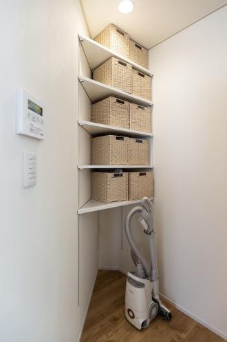 洗濯コーナーの斜めの壁の反対側には、キッチン用の棚を造作。デッドスペースをつくらない素敵なアイデアです