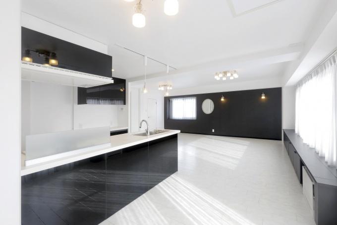 バルコニーから差し込む光がさらに華やかさを添えて。輝くばかりの白い空間に壁やキッチンの黒が効果的な彩色
