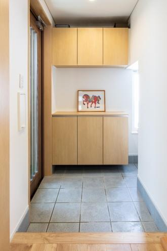 玄関収納を上下セパレートタイプに変えて光が玄関の中へと差し込むように