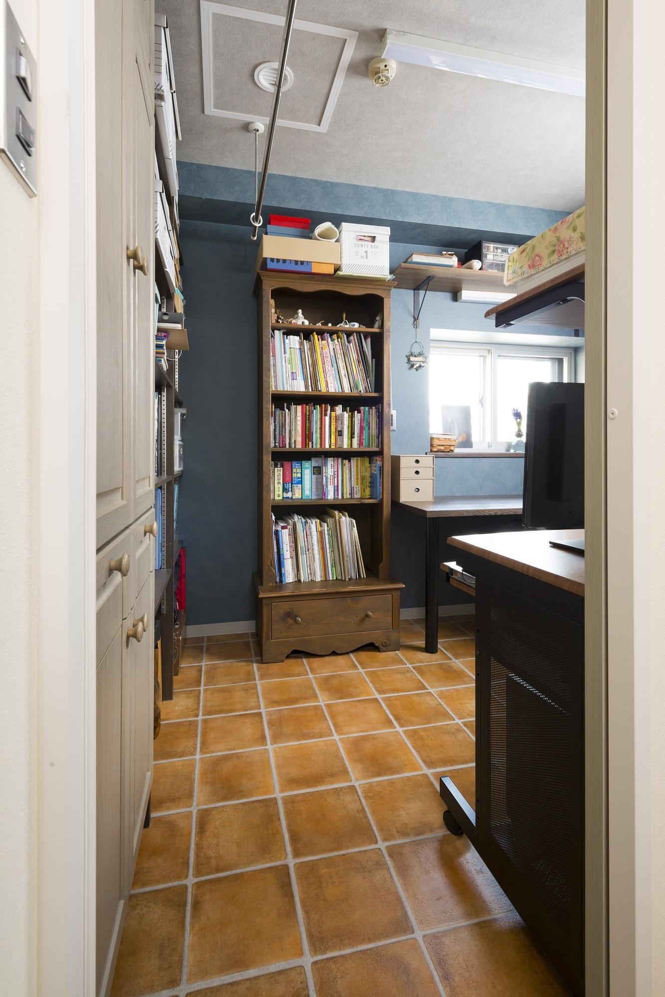 水回り側の入口から見た奥さまのアトリエ兼パントリー。床はキッチンまで同じテラコッタ風のフロアで、壁は奥さまが好きなブルーに