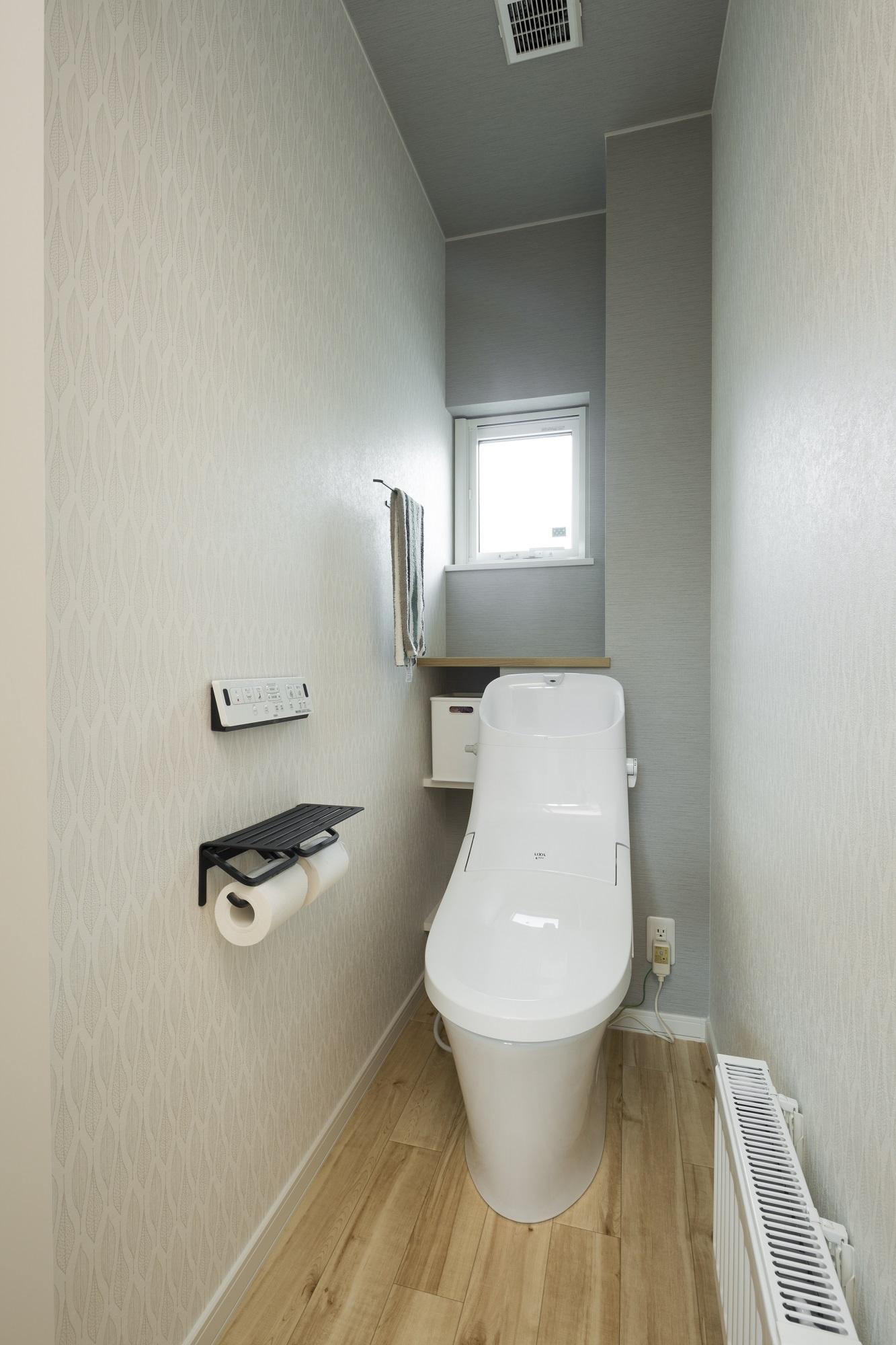 背面に薄いグレーのクロスを貼って、優しくアクセントを付けた2階のトイレ