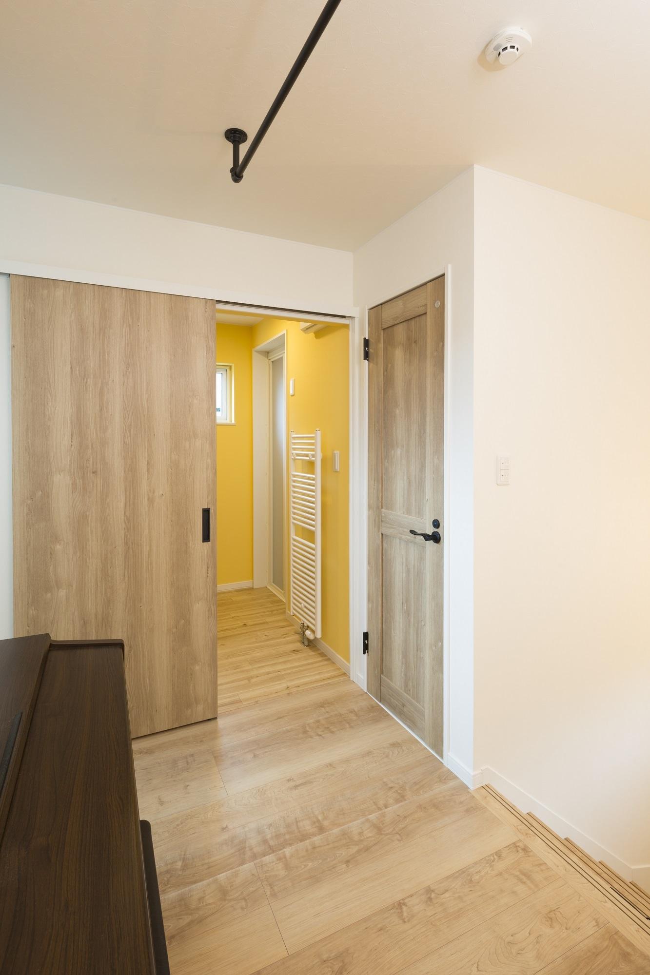 元気が出るビタミンカラーの壁の脱衣室と浴室は2階に配置。ホールには洗濯物が干せるようにポールも設置