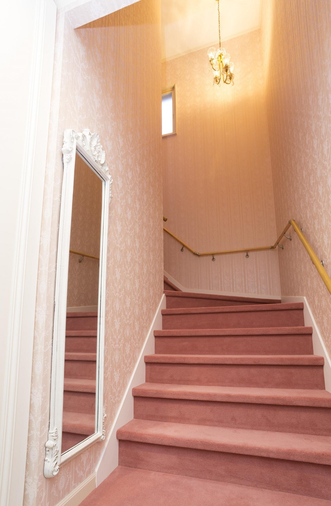 2階住居部へつながる室内ドアは既存を塗り直して流用。リビングのサーモンソファと同系色のカーペットで階段にも統一感
