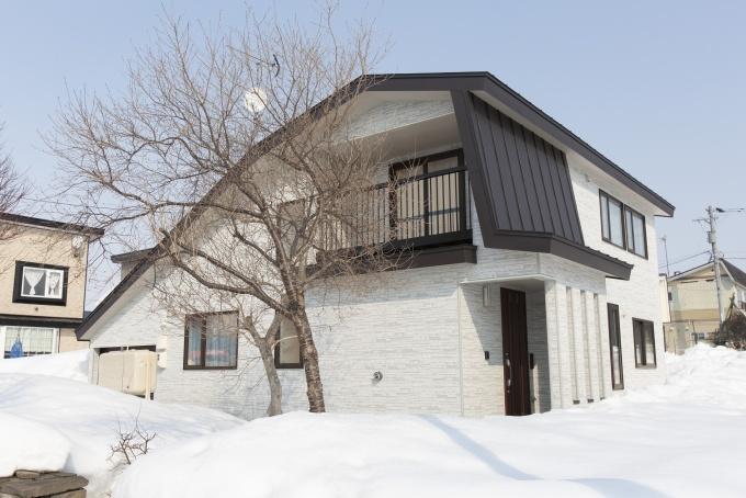 明るい壁に濃茶の屋根や窓枠のコントラストが美しい外観