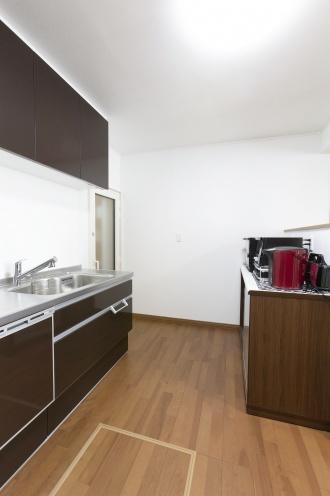 シックな色合いのシステムキッチン。調理家電を置く棚は、事前に寸法を伝えてリビングから見えない高さに設計してもらいました