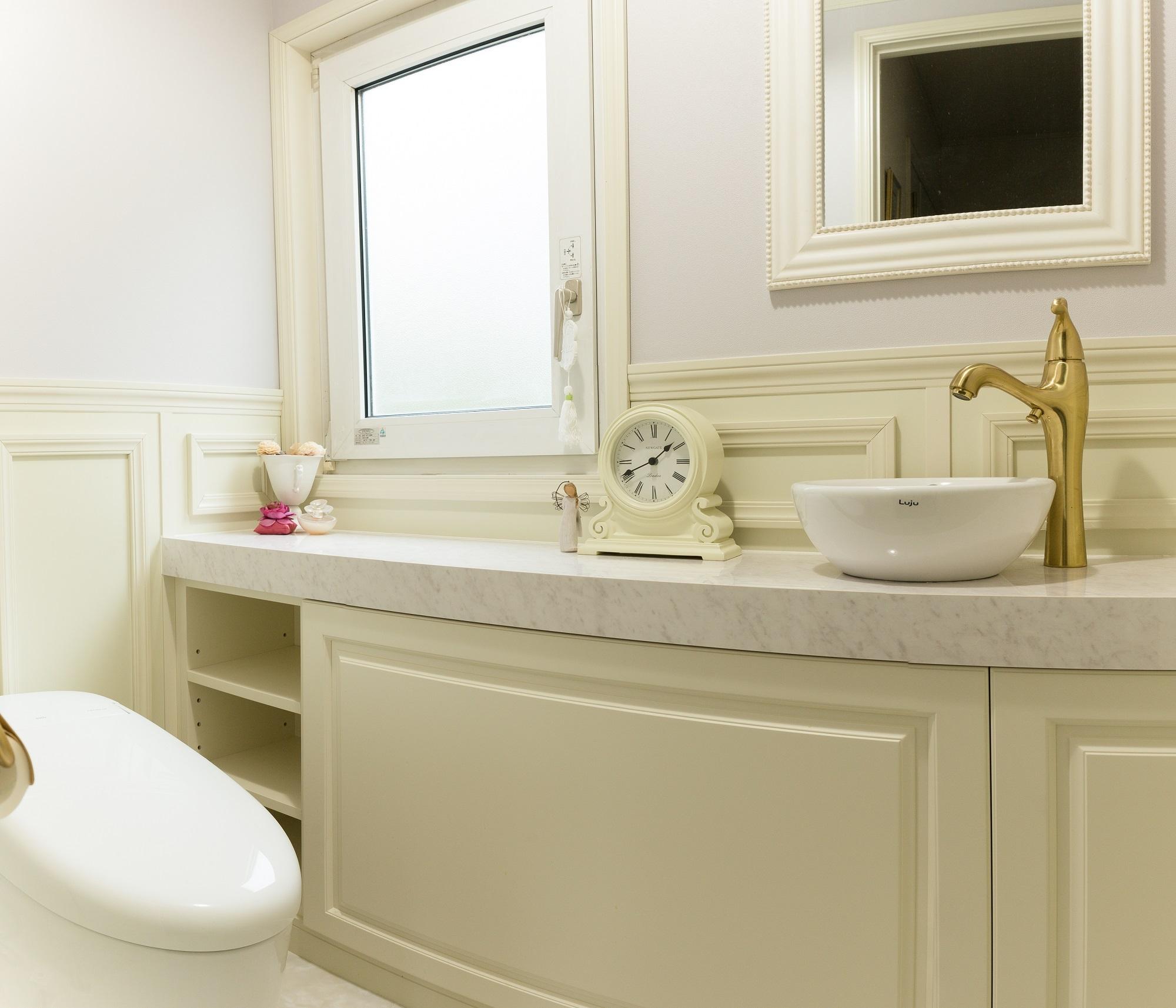 造作の四方枠や人工大理石で豪華さを演出したトイレ