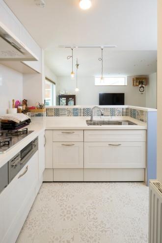 白いキッチンに映えるブルー基調の8種類のタイルがアクセントを添えて