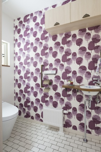 1階トイレは車イスも入れる広さを希望。紫色の木が楽しげなクロスは、フィンランドの老舗・フィンレイソンのデザイン。サブウェイタイルを模したフロアとのマッチングが、とてもモダンです